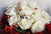Gold wedding rings on a bouquet of beige roses — Fotografia Stock