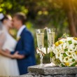 Wedding rings with roses and glasses of champagne and a kiss of the groom and bride on a background — Stock Photo #62019703