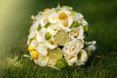 Wedding bouquet from beige roses, cinnamon, a lemon, a lime on a green grass — Stock Photo