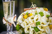 Wedding rings with wedding bouquet from beige roses, cinnamon, a lemon, a lime and glasses of champagne — Foto Stock