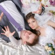 Beautiful young couple lying on bed in the bedroom — Foto de Stock   #62028695