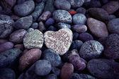 Single  heart on black pebble stones — Stock Photo