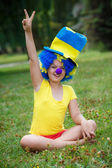 Girl is sitting on the grass in clown wig and hat — Stock Photo