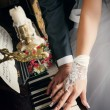 Hands of married man and woman with wedding rings laying on keys of piano with beige roses nearly — Stock Photo #77107973