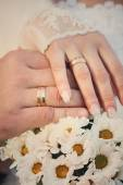Bride and groom hands with wedding rings and bouquet of white chrysanthemums — Stock Photo
