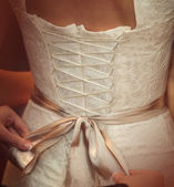 Bride is putting on her white wedding dress — Stock Photo