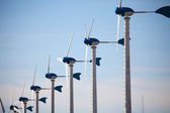 Green renewable energy concept - wind generator turbines on blue — Stock Photo