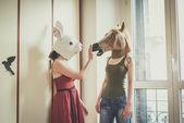 Mask rabbit and horse mask lesbian couple — Stock Photo