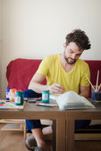 Handsome hipster modern man painting — Stock Photo