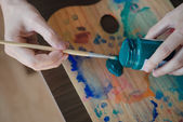 Close up hands using paintbrush and colours — Stockfoto