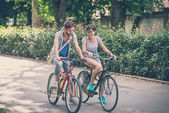 Couple of friends young  man and woman riding bike — Stock Photo