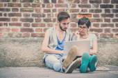 Couple of friends young  man and woman using laptop — Stock Photo