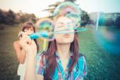 Beautiful hipster young women sisters friends blowing bubbles — Stockfoto