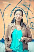 Beautiful african young woman listening music earphones — Stock Photo