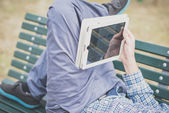 Close up hands man using tablet lying on a bench — Stock Photo