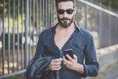 Bearded model man using smartphone — Stock Photo
