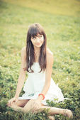 Beautiful young woman with white dress listening music — Foto de Stock