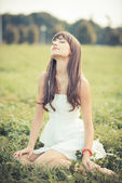 Beautiful young woman with white dress listening music — Photo