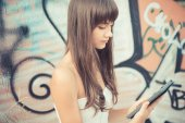 Beautiful young woman with white dress using tablet  — Stock Photo