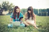 Siostry za pomocą tabletki i smartphone w parku — Zdjęcie stockowe