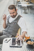 Handsome big moustache hipster man using tablet — Stock Photo