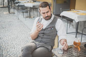 Handsome big moustache hipster man using smart phone — Stock Photo