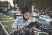 Hipster gay in hat using digital tablet — Stok fotoğraf