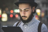 Hipster gay in hat using digital tablet — Stock Photo