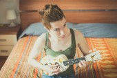 Young lesbian stylish hair style woman playing guitar — Stock Photo