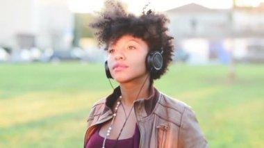 Happy african girl listening music — Stock Video