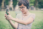 Young hipster woman listening to music selfie — Stock Photo