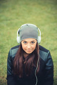 Young girl in park listening music — Stock Photo