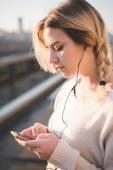 Blondýnka venkovní poslech hudby — Stock fotografie
