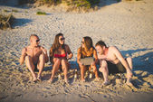 Young friends on summer beach — Stock Photo