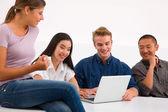Group of happy friends using laptop — Foto de Stock