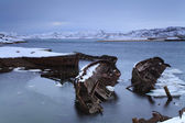 View of snow-covered shore with old boats — Stockfoto