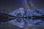 Amazing night landscape with mountains and stars. Reflection of  — Stock Photo