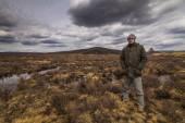 Man traveler on marshland against the backdrop of rain clouds. — Stock Photo