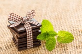 Mint leaves and chocolate underneath burlap. — Stock Photo