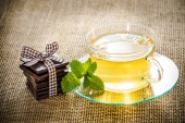 Glass tea cup mint leaves and chocolate. — Stock Photo