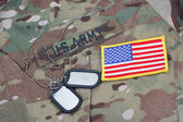 Us army camouflaged uniform with US flag patch and blank dog tags — Stock Photo