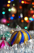 Christmas balls on the background of colored lights — Stock Photo
