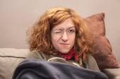 Redhead woman with one eye closed relaxing on sofa — Stock Photo
