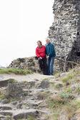 Happy senior couple hiking on rocky terrain — Stock Photo