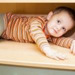 Child boy hiding in cupboard — Stock Photo #70262789