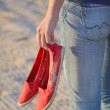 Girl in blue jeans holding red slippers on the beach — Stock Photo #68125803