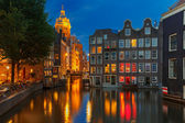 Night city view of Amsterdam canal, church and bridge — Stock Photo