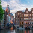 Evening city view of Amsterdam canal, church and bridge — Stock Photo #53730137