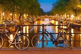 Natt belysning av amsterdams kanaler och bridge — Stockfoto