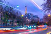 Cityscape with the shimmering Eiffel Tower and night street in Paris, France — Stockfoto